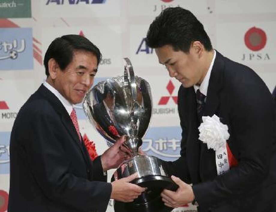 Masahiro Tanaka, right, star pitcher of Japanese baseball club Rakuten Golden Eagles receives the grand prix trophy from Japan's Education Culture, Sport Science and Technology Minister Hakubun Shimomura, left, during the awarding ceremony of the Japan Professional Sports award in Tokyo, Friday, Dec. 27, 2013.