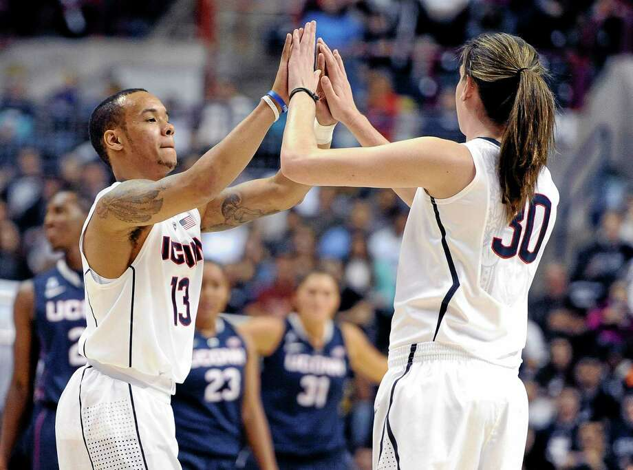 UConn's Shabazz Napier, left, high-fives teammate Breanna Stewart during an inter-squad scrimmage at the men's and women's basketball teams' First Night event in Storrs on Friday. Photo: Jessica Hill — The Associated Press  / FR125654 AP