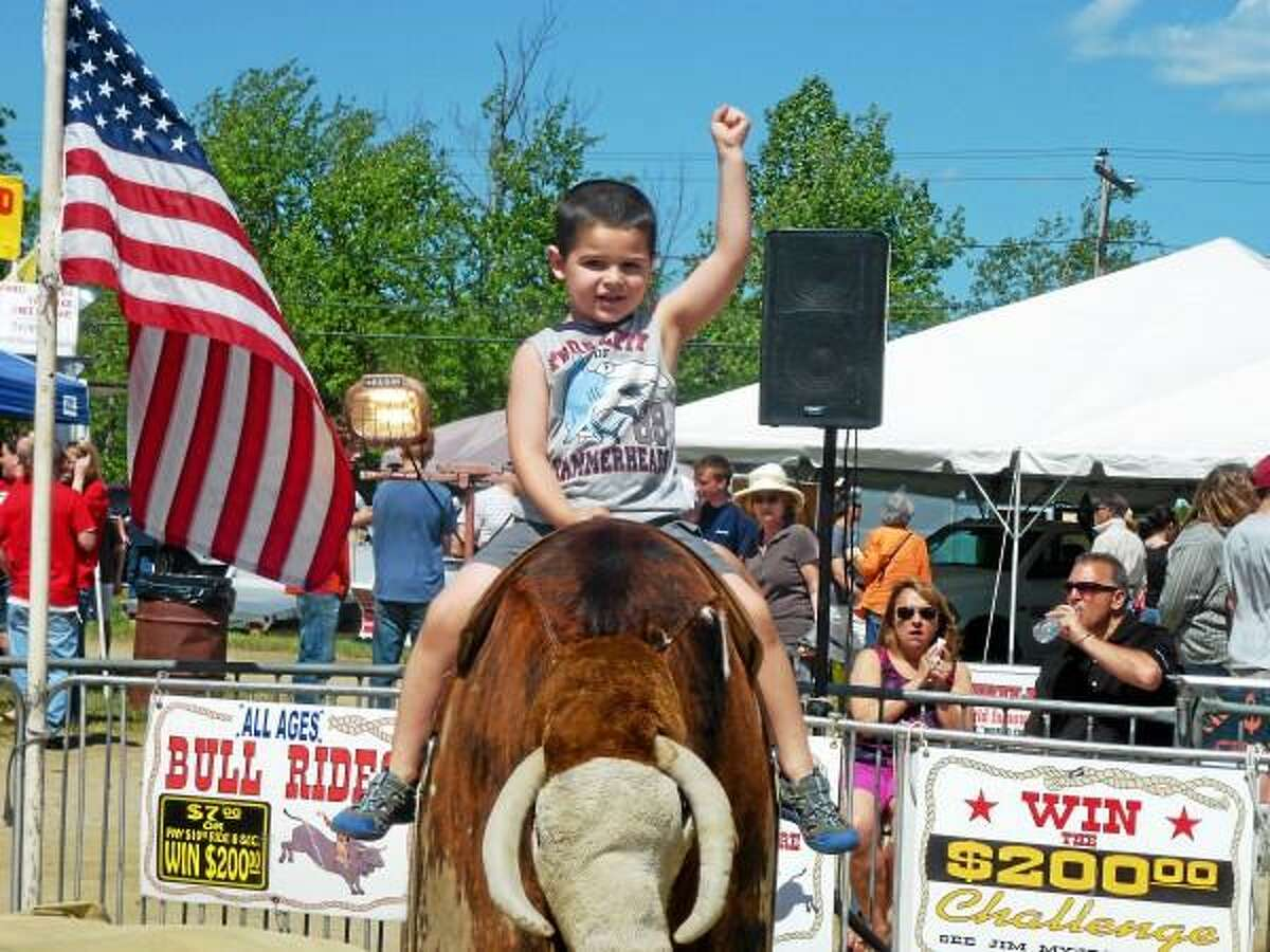 Surrounded by a crowd of smiling spectators, children and adults alike tried their best to stay on the mechanical bull at the 2013 Goshen Stampede. (Ryan Flynn-Register Citizen)
