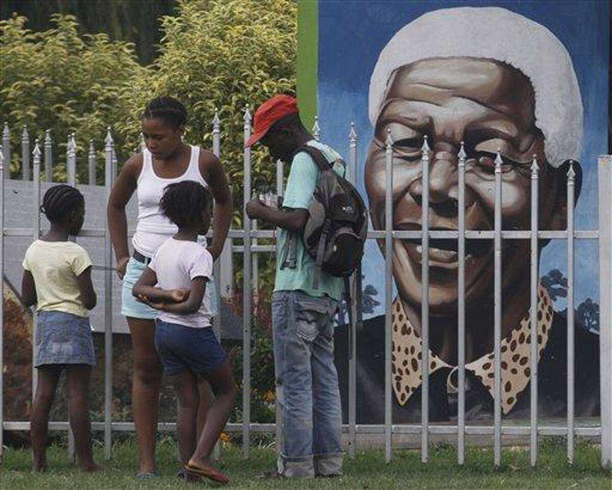 Visitors gather in front of a portrait of former president Nelson Mandela, in a Park in Soweto, South Africa, Thursday, March, 28, 2013. 94-year-old Mandela, the anti-apartheid leader who became South Africa's first black president, has been hit by a lung infection again and is in a hospital, the presidency said. Mandela, has become increasingly frail in recent years and has been hospitalized several times in recent months, including earlier this month when he underwent what authorities said was a scheduled medical test. The Nobel laureate is a revered figure in South Africa, which has honored his legacy of reconciliation by naming buildings and other places after him and printing his image on national banknotes. (AP Photo/Denis Farrell)