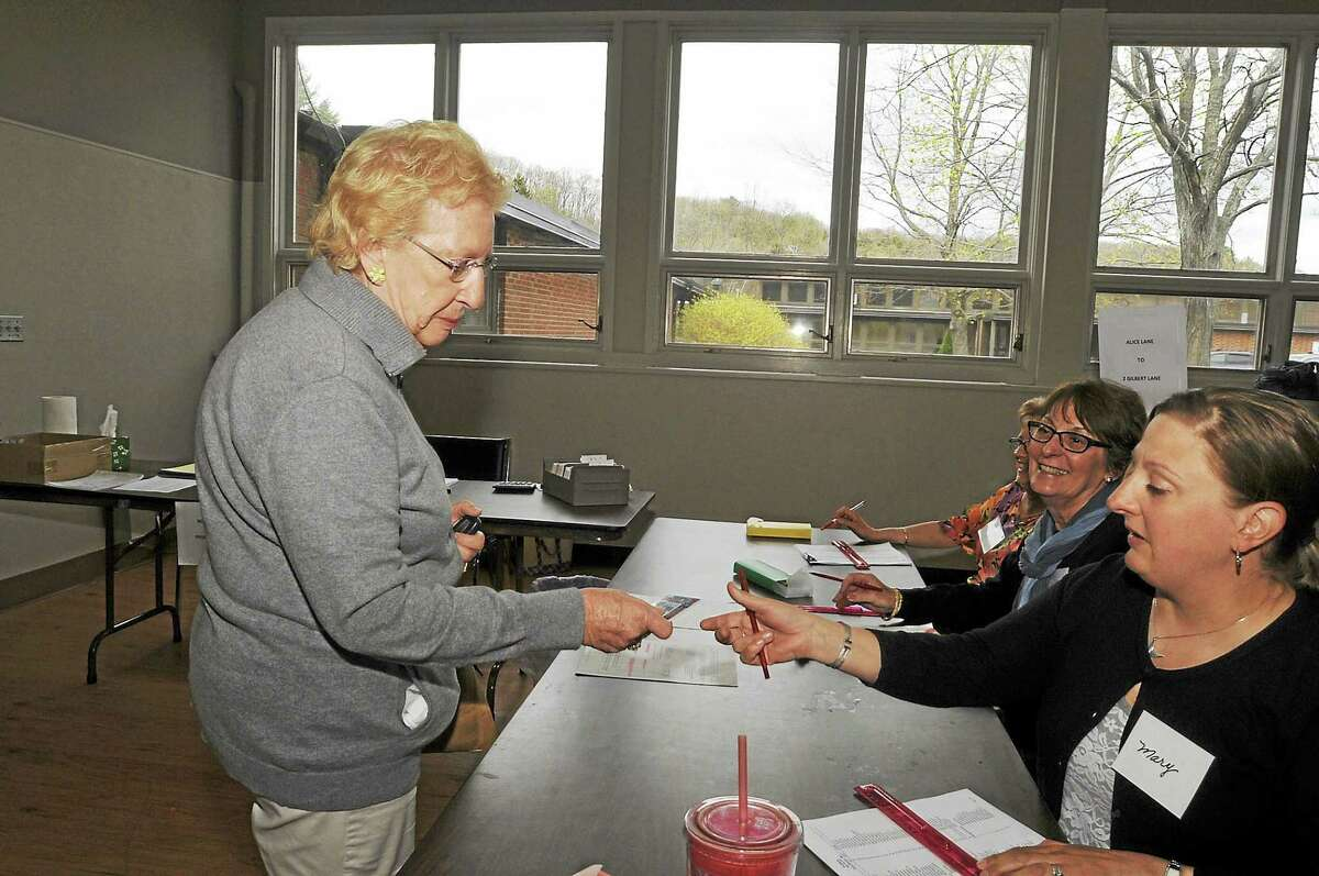 Gloria Benedict checks in to vote in Burlington Tuesday as the town residents vote on the proposed budget for Region 10.