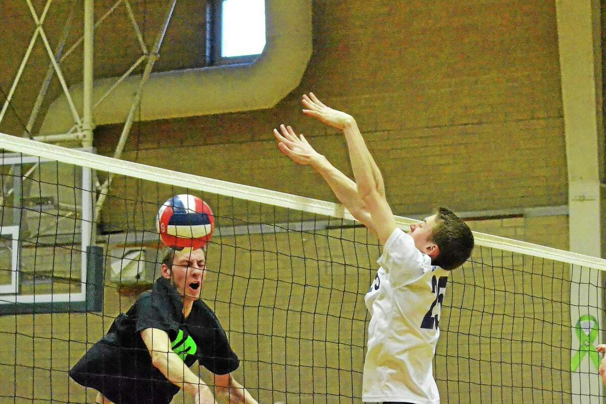 Wolcott Tech's Tyler Kackowski reacts after Lewis Mills' Tim Forella blocks one of his spikes.