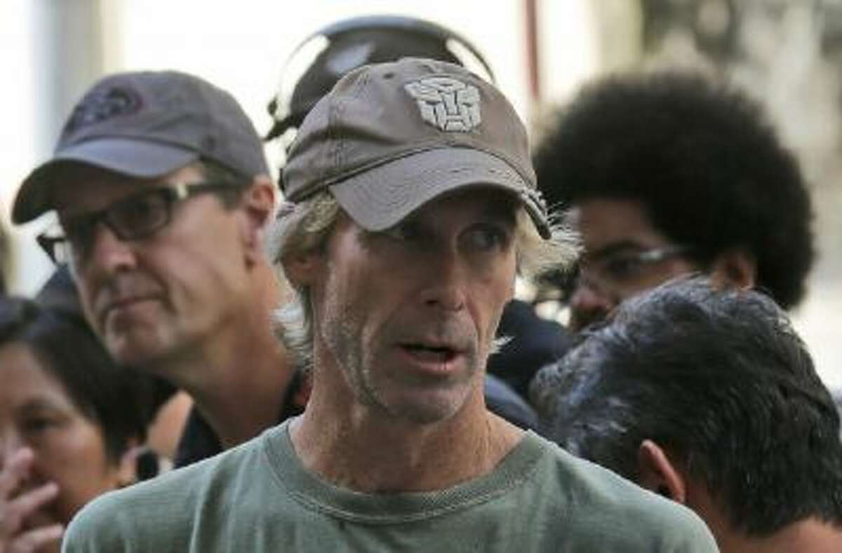"""American film director Michael Bay speaks with his film crew during the filming of a scene for their latest movie """"Transformers 4: Age of Extinction"""" in Hong Kong Friday, Oct. 18, 2013."""