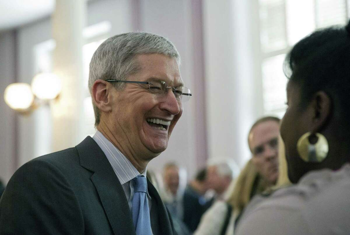 Apple chief executive and Alabama native Tim Cook laughs with a group before an Alabama Academy of Honor ceremony at the state Capitol on Oct. 27, 2014, in Montgomery, Ala. Cook and seven others including University of Alabama football coach Nick Saban were inducted into the Alabama Academy of Honor.