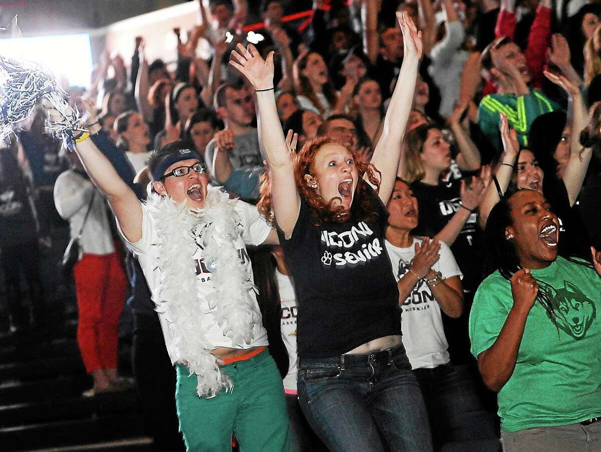 Husein Becirovic of New Britain, Conn., left, Laura Purcell of Stoughton, Mass., center, and Yvonne Ambenge of Mansfield, Conn., right, cheer as they watch the broadcast of the UConn and Notre Dame women's basketball game for the NCAA title on April 8, 2014, in Storrs, Conn.