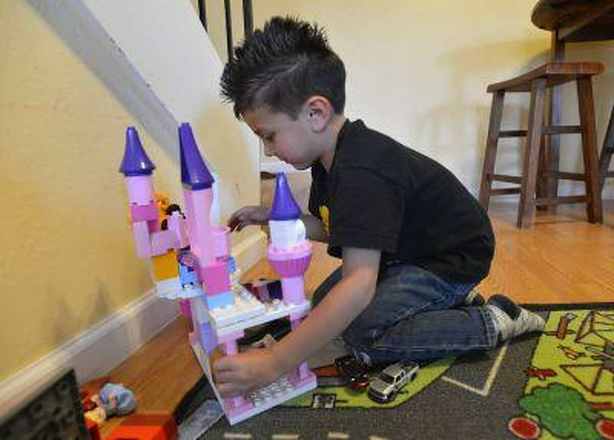 Julian Meija-Blagovic, 4, of Martinez, plays with a Duplo Lego Castle that was given to his parents for their five-month-old daughter in Martinez, Calif., on Saturday March 23, 2013. His parents, Jorge Meija and Lisa Blagovic, are trying to raise their kids with respect and balance of gender.