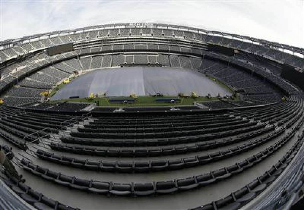 In this photograph taken with a fisheye lens, a tarp covers the field at MetLife Stadium in an effort by crews to keep the turf dry ahead of Super Bowl XLVIII, Wednesday, Jan. 15, 2014, in East Rutherford, N.J. Among other preparations, crews are setting up a perimeter 300 feet from the entrances to the stadium as a security measure. Police officials say security for the Super Bowl will include about 4,000 government and private officers assigned to the stadium on game day.