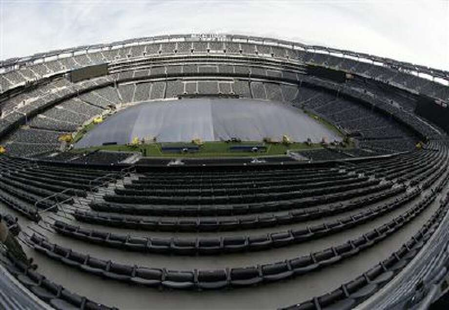 In this photograph taken with a fisheye lens, a tarp covers the field at MetLife Stadium in an effort by crews to keep the turf dry ahead of Super Bowl XLVIII, Wednesday, Jan. 15, 2014, in East Rutherford, N.J. Among other preparations, crews are setting up a perimeter 300 feet from the entrances to the stadium as a security measure. Police officials say security for the Super Bowl will include about 4,000 government and private officers assigned to the stadium on game day. Photo: AP / AP