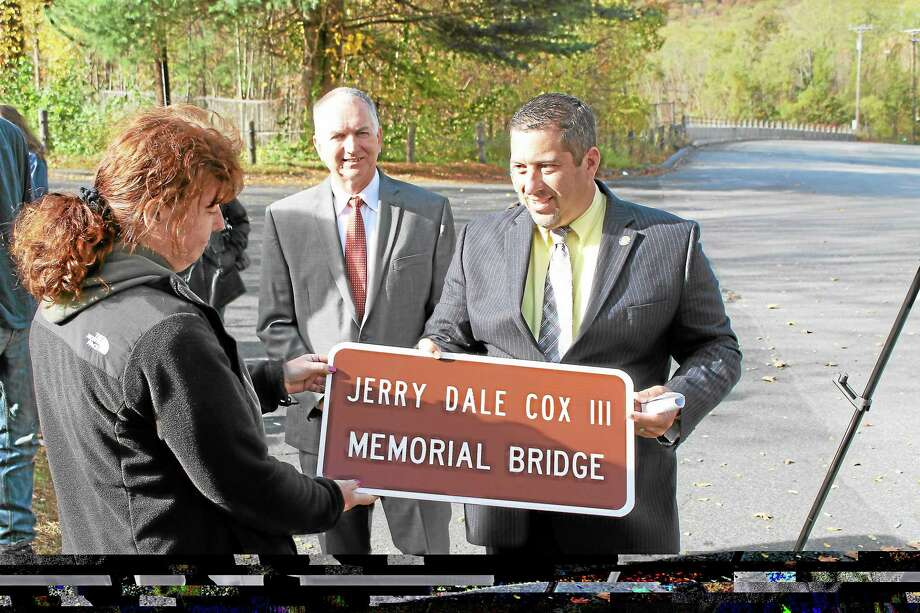 State Rep. Jay Case presents a sign which dedicated the Greenwoods Road bridge in memory of Jerry Dale Cox III, who was killed in a nearby car crash in December 2010. Photo: Contributed Photo