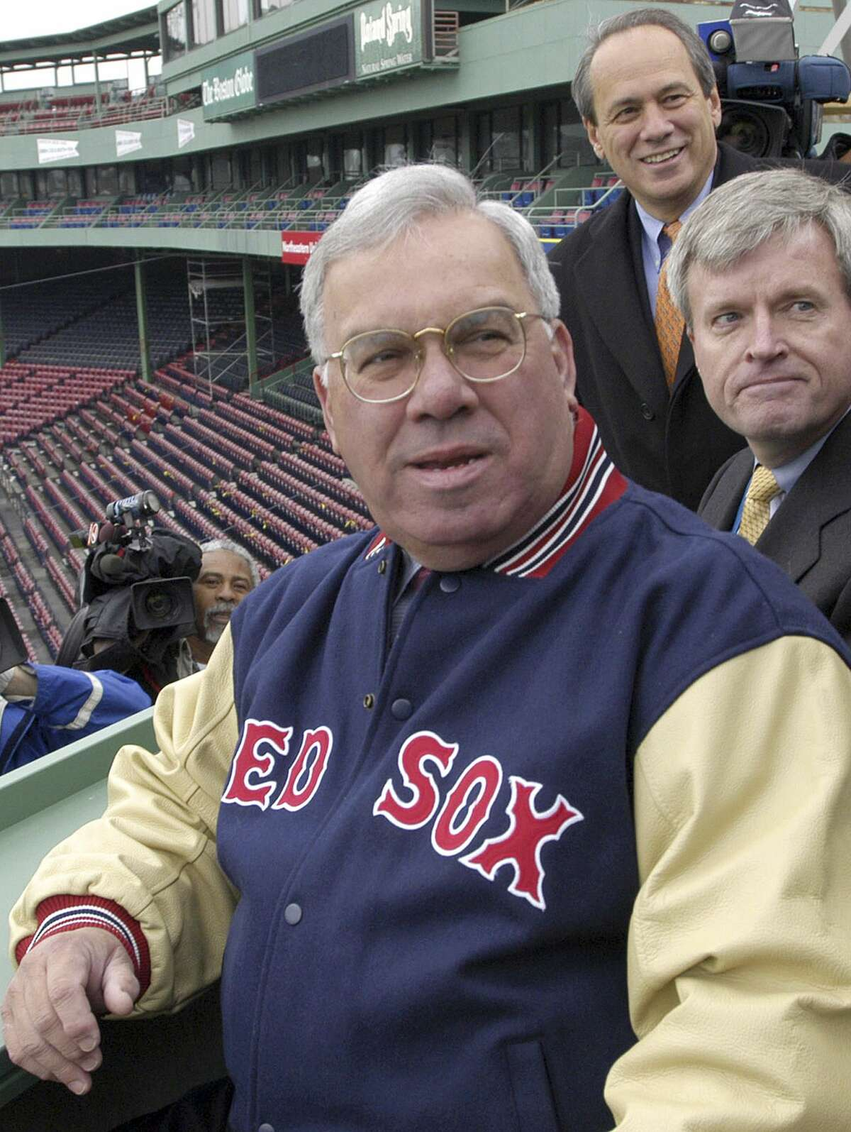 """FILE - In this April 3, 2003 file photo, Boston Mayor Thomas Menino, foreground, is given a tour of the new seating area above the """"Green Monster"""" left field wall at Fenway Park, home of the Boston Red Sox, in Boston. With Menino are city official Mike Galvin, right, and Red Sox President and CEO Larry Lucchino, rear. Menino, who was diagnosed with cancer a month after leaving office in 2013, died Thursday, Oct. 30, 2014 in Boston. He was 71. (AP Photo/Josh Reynolds, File)"""