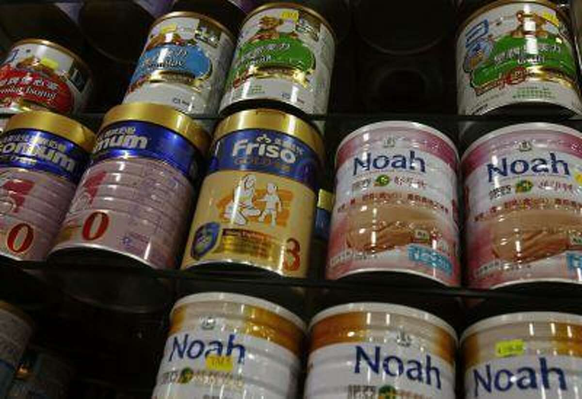 Baby milk formula brands are displayed inside a pharmacy.