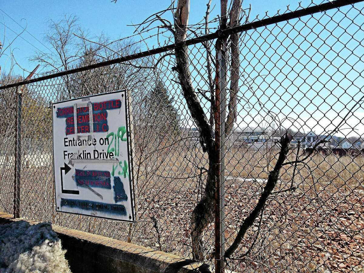 A sign is attached on the fence bordering the property on 100 Franklin Street on Tuesday, March 18, 2014, in Torrington. The property was purchased by the city for $1 last year and will require extensive redevelopment before it can be reused. Esteban L. Hernandez Register Citizen