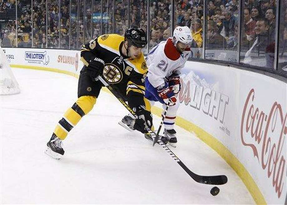 Boston Bruins' Zdeno Chara (33), of Slovakia,  battles Montreal Canadiens' Brian Gionta (21) for the puck in the first period of an NHL hockey game in Boston, Wednesday, March 27, 2013. (AP Photo/Michael Dwyer) Photo: ASSOCIATED PRESS / AP2013