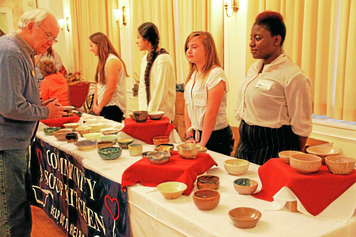 Volunteers hand out soup to community members who came to the Empty Bowls fundraiser for the Community Soup Kitchen of Torrington on Wednesday.