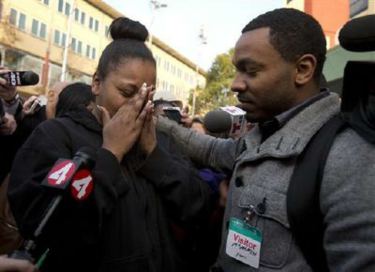 Nailah Winkfield, left, mother of 13-year-old Jahi McMath, is comforted as she talks to the media outside Children's Hospital Oakland in Oakland, Calif.