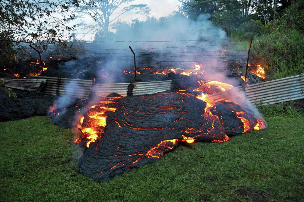 This Tuesday, Oct. 28, 2014 photo provided by the U.S. Geological Survey shows lava that has pushed through a fence marking a property boundary above the town of Pahoa on the Big Island of Hawaii. After weeks of slow, stop-and-go movement, a river of asphalt-black lava was less than the length of a football field from homes in the Big Island community Tuesday. The lava flow easily burned down an empty shed at about 7:30 a.m., several hours after entering a residential property in Pahoa Village, said Hawaii County Civil Defense Director Darryl Oliveira. A branch of the molten stream was less than 100 yards (90 meters) from a two-story house. It could hit the home later Tuesday if it continues on its current path, Oliveira estimated. Residents of Pahoa Village, the commercial center of the island's rural Puna district south of Hilo, have had weeks to prepare for what's been described as a slow-motion disaster. Most have either already left or are prepared to go. (AP Photo/U.S. Geological Survey)