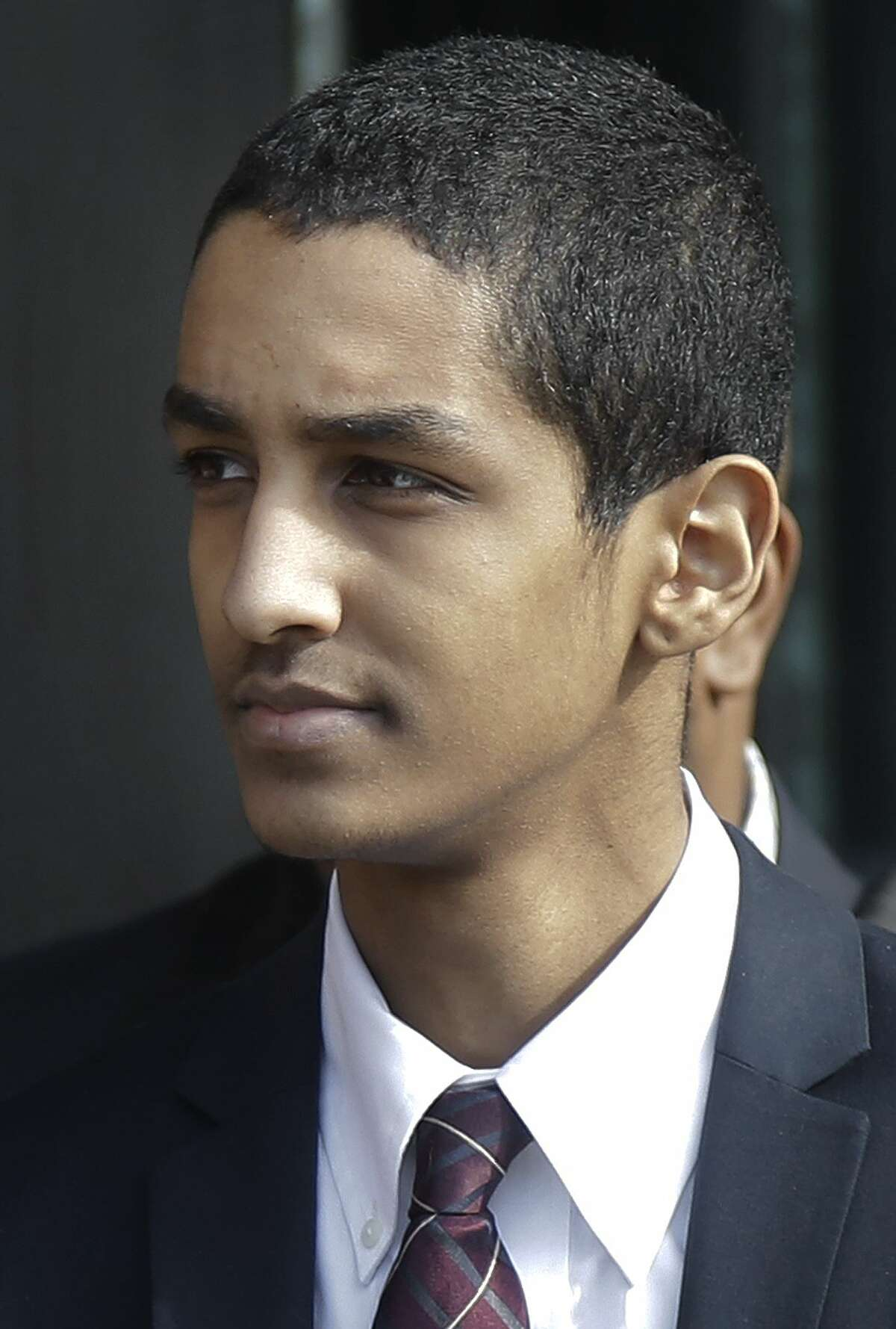 Robel Phillipos departs federal court after he was convicted in Boston Tuesday, Oct. 28, 2014 on two counts of lying about being in the dorm room of Boston Marathon bombing suspect Dzhokhar Tsarnaev three days after the bombing in 2013, while two other friends removed a backpack containing fireworks and other potential evidence. (AP Photo/Stephan Savoia)