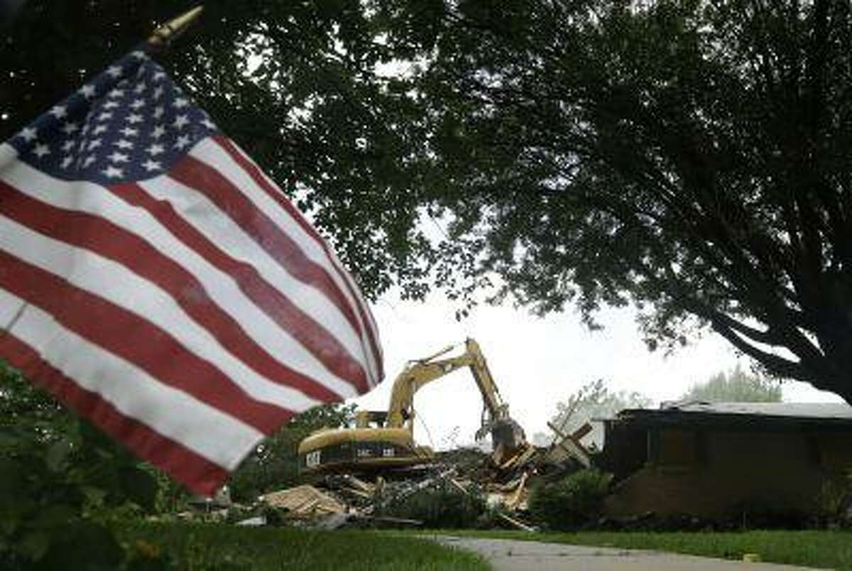 An American flag planted by the curb in front of this home waves in the breeze as tractor operator Jeff Holveck, a volunteer from Cleburne, Texas, demolishes the home Friday, May 31, 2013, in West, Texas. The white slabs popping up across town are a sign that the effort to rebuild West has just begun, almost two months after an explosion that killed 15, and injured 200. (AP Photo/Tony Gutierrez)