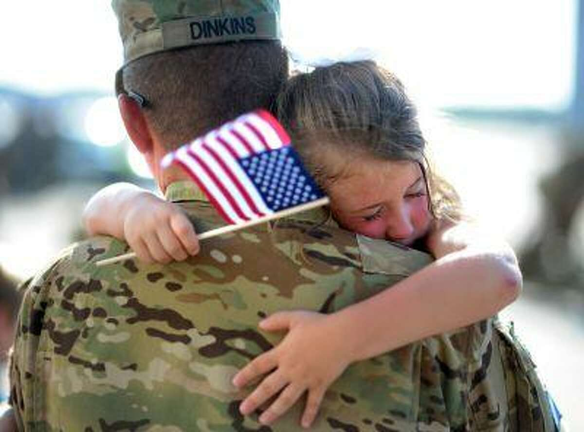 U.S. Army Staff Sgt. Jason Dinkins with the 3rd Combat Aviation Brigade is hugged by his daughter Olivia Chastain after a welcome home ceremony, Tuesday, June 11, 2013 at Hunter Army Airfield in Savannah, Ga. The aviation brigade deployed 2,200 soldiers to Afghanistan in December on a 9-month mission, but came home earlier than expected because of the readiness of the Afghan National Security. (AP Photo/Stephen Morton)