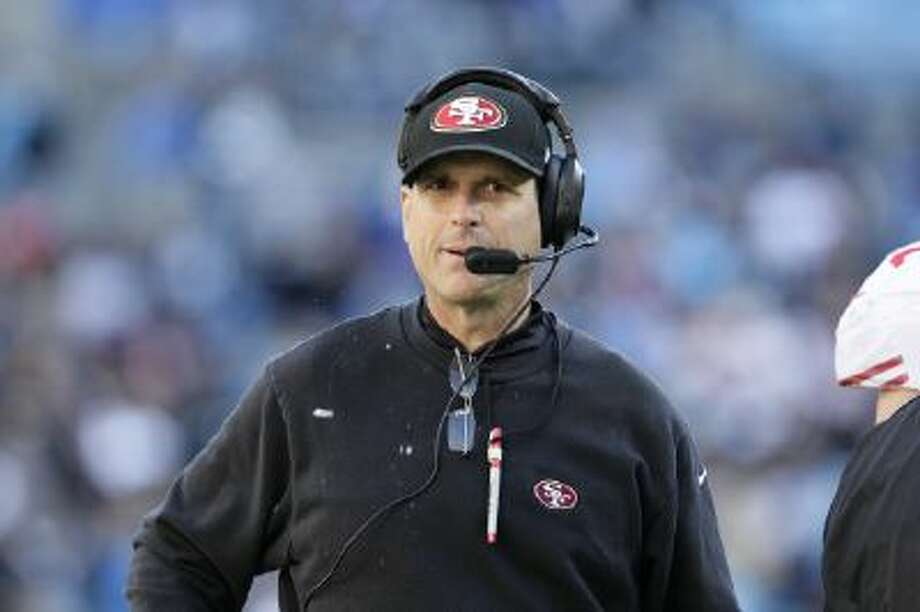 San Francisco 49ers head coach Jim Harbaugh walks the sidelines against the Carolina Panthers during the second half of a divisional playoff NFL football game, Sunday, Jan. 12, 2014, in Charlotte, N.C.