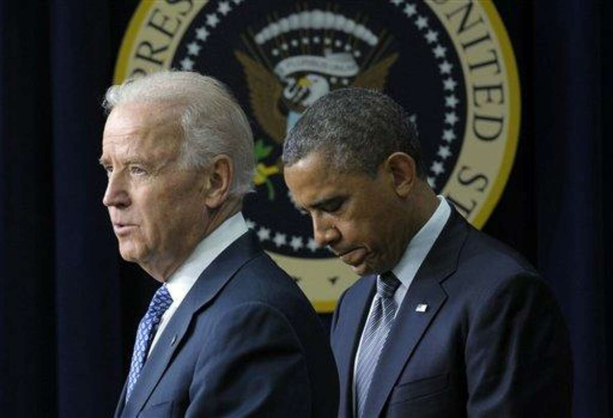 FILE - In this Jan. 16, 2013 file photo, President Barack Obama listens as Vice President Joe Biden speaks in the South Court Auditorium at the White House in Washington, about proposals to reduce gun violence. President Barack Obama promised after the Newtown shootings to put his full weight behind gun control, but so far that means not doing too much that could get in the way of delicate negotiations over the legislation on Capitol Hill. The president has not been highly visible in the gun debate during the past three weeks, a critical time when the bills are taking shape. He's been embroiled in a budget battle that has dominated his time and for now is letting Vice President Joe Biden take the White House lead in the campaign for tighter firearm laws. (AP Photo/Susan Walsh, File)