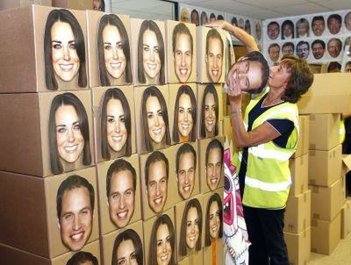 Pam Cooper from the Mask-arade mask company loads boxes of Prince William and Kate, Duchess of Cambridge masks ready for dispatch at the company works in Southam , England Thursday June 6, 2013. Mask-arade are in overdrive printing masks of Kate and William for the street parties that will follow the announcement of the birth of the Royal baby, expected in July. Normally, the company has 2,000 masks on hand. But for the royal birth, they will whip up 20,000 to meet the expected demand.