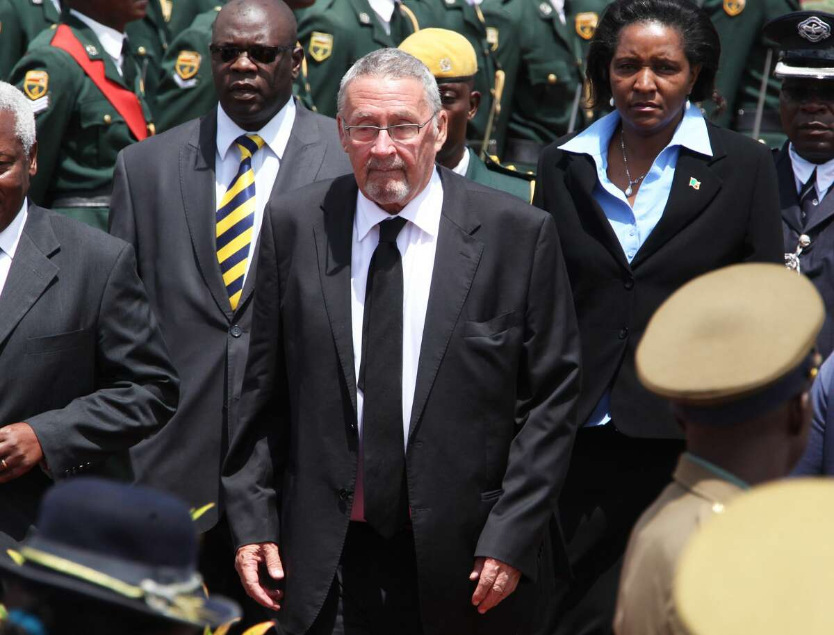 FILE - In this Monday, Jan 21, 2014 file photo Zambian deputy president Guy Scott, centre, attends the burial of Zimbabwe's deputy president John Nkomo, at the Heroes Acre, in Harare, Zimbabwe. Following the death of Zambian President Michael Sata, the Zambian government says Guy Scott will become acting president of the southern African nation until new elections are held within 90 days. President Michael Sata, who had been gravely ill in a London hospital, died late Tuesday. (AP Photo/Tsvangirayi Mukwazhi, FILE)