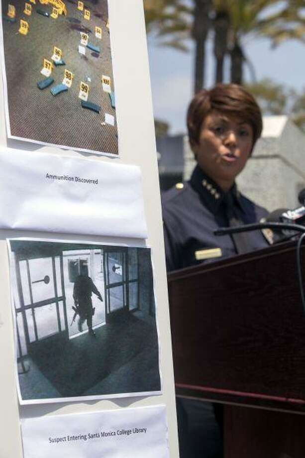 A picture of the suspect entering Santa Monica College Library is seen as Jacqueline Seabrook, Chief of Santa Monica Police department speaks during a news conference Saturday June 8, 2013, in Santa Monica, Calif., to discuss more information regarding the suspect in the shooting that left five people dead, including the shooter, near Santa Monica College on Friday. (AP Photo/Ringo H.W. Chiu) Photo: AP / FR170512 AP
