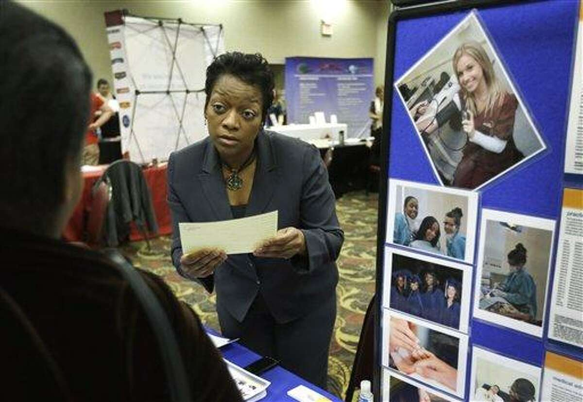 In this Feb. 28, 2013 photo Shawn Gordon, corporate presenter of the Dorsey Schools listens to a job applicant at the JobFairGiant.com employment fair in Dearborn, Mich. Fewer Americans sought unemployment aid last week, reducing the average number of weekly applications last month to a five-year low. The drop shows that fewer layoffs are strengthening the job market. The Labor Department said Thursday, March 14, 2013 that applications fell 10,000 to a seasonally adjusted 332,000. That cut the four-week average to 346,750, the lowest since March 2008, just several months after the Great Recession began. (AP Photo/Carlos Osorio)