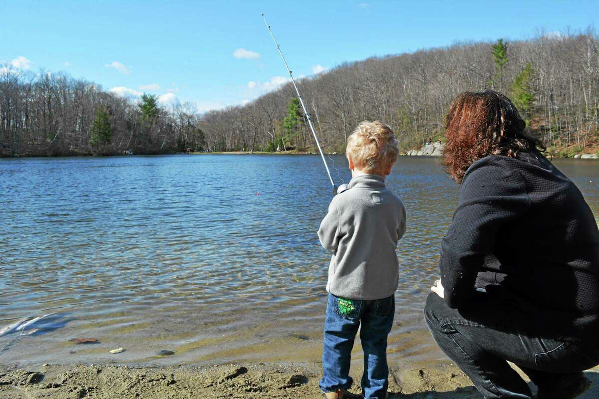 Debbie Alduini helps her 3-year-old son Landon fish in the Elks Lodge's 44th annual children's fishing derby Sunday at Elks Pond in Torrington. This was Landon's first time fishing. John Berry - The Register Citizen