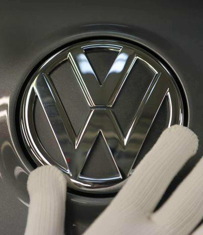 """ARCHIV - Ein Arbeiter montiert am 29. Oktober 2008 im Volkswagen-Werk in Zwickau das VW-Logo an einem Golf. Der insolvente Zulieferer Karmann hat laut einem Bericht einen millionenschweren Auftrag von VW erhalten und kann damit seine Transfergesellschaft fuer 1.540 gekuendigte Mitarbeiter finanzieren. Fuer den Entwicklungsauftrag in zweistelliger Millionenhoehe zahle VW Vorkasse und habe so die Gruendung der Transfergesellschaft ermoeglicht, berichtete die """"Neuen Osnabruecker Zeitung"""" am Freitag, 3. Juli 2009. (AP Photo/Eckehard Schulz) ** zu APD9716 ** -- FILE - An Oct 29, 2008 file picture shows a worker fixing a VW logo at a Golf VI at the assembly line of the Volkswagen plant in Zwickau, eastern Germany. (AP Photo/Eckehard Schulz)"""