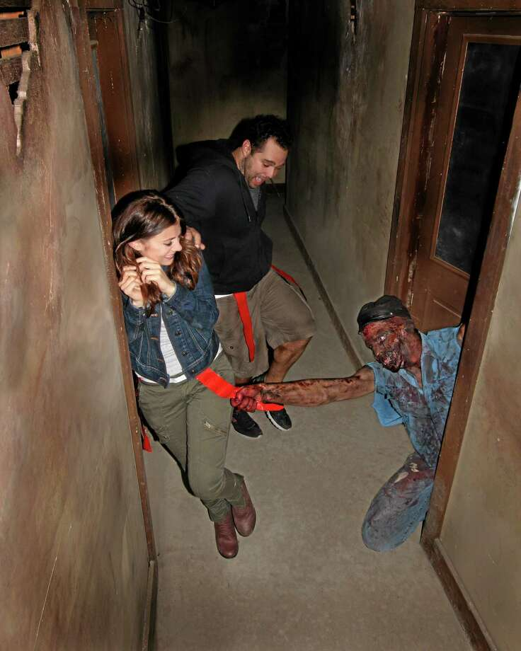 This August 2013 image, provided by Shocktoberfest, shows an actor portraying a zombie who grabs a flag from the belt of someone walking through the Prison of the Dead Escape, part of the Shocktoberfest attraction in Reading, Pa. The scene is considered tame compared to the realistic tableau in Mustang, Okla., where some residents find the display disturbing. (AP Photo/Shocktoberfest) Photo: AP / Shocktoberfest