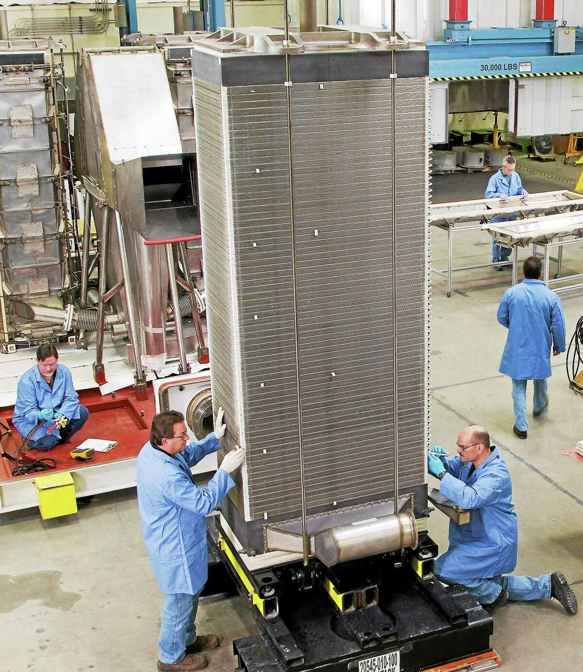 Employees at work inside the FuelCell Energy manufacturing facility in Torrington. On Wednesday, the company announced plans for a $65 million two-phased expansion to the facility and expects to create up to 325 jobs over four years.