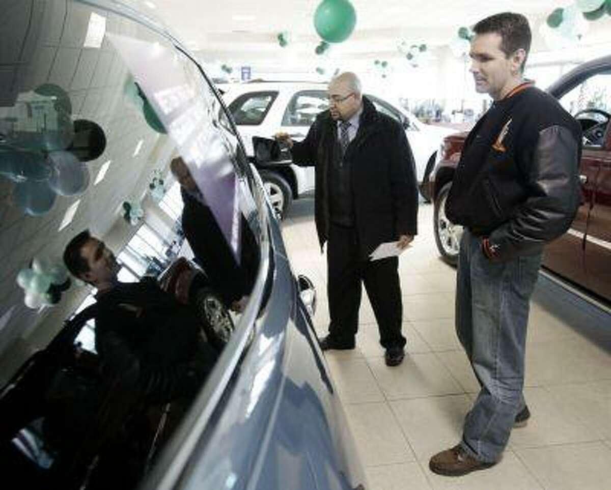 """FILE - In this Feb. 27, 2009 file photo, Jerry Mulvihill, second from left, of Alsip, Ill., talks with car salesman Gerardo Rangel at the Apple Chevrolet dealership in Orland Park, Ill. """"The Big Three (Chrysler, Ford and Chevrolet) have quietly restarted their leasing programs, even expanding them to include smaller or mid-size vehicles to encourage people back into cars,"""" says Mark Guarino, an auto analyst for Chicago-based market research company Mintel International.(AP Photo/Charles Rex Arbogast, file)"""