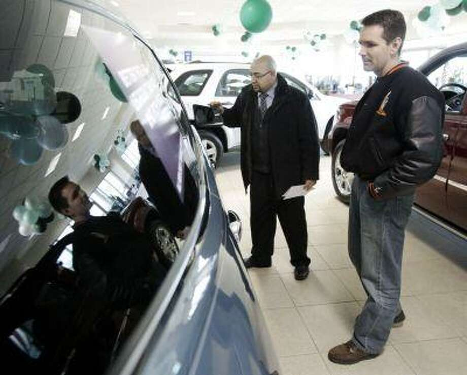"""FILE - In this Feb. 27, 2009 file photo, Jerry Mulvihill, second from left, of Alsip, Ill., talks with car salesman Gerardo Rangel at the Apple Chevrolet dealership in Orland Park, Ill. """"The Big Three (Chrysler, Ford and Chevrolet) have quietly restarted their leasing programs, even expanding them to include smaller or mid-size vehicles to encourage people back into cars,"""" says Mark Guarino, an auto analyst for Chicago-based market research company Mintel International.(AP Photo/Charles Rex Arbogast, file) Photo: ASSOCIATED PRESS / AP2009"""