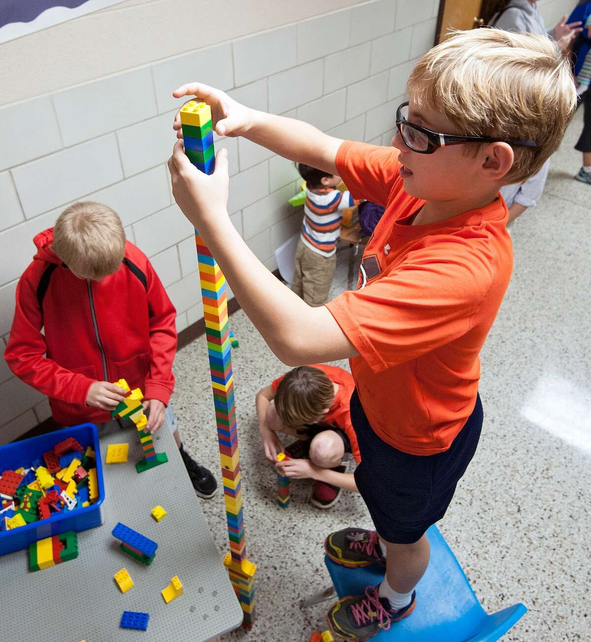 Jax Lassiter, 11, of Bridgewater, precariously adds another Lego to his tower just moments before its collapse during STEAM night (Science, Technology, Engineering, Arts, and Mathematics) at John Wayland Elementary School in Bridgewater, Va., on Thursday night, Oct. 16, 2014. (AP Photo/The Daily News-Record, Jason Lenhart)