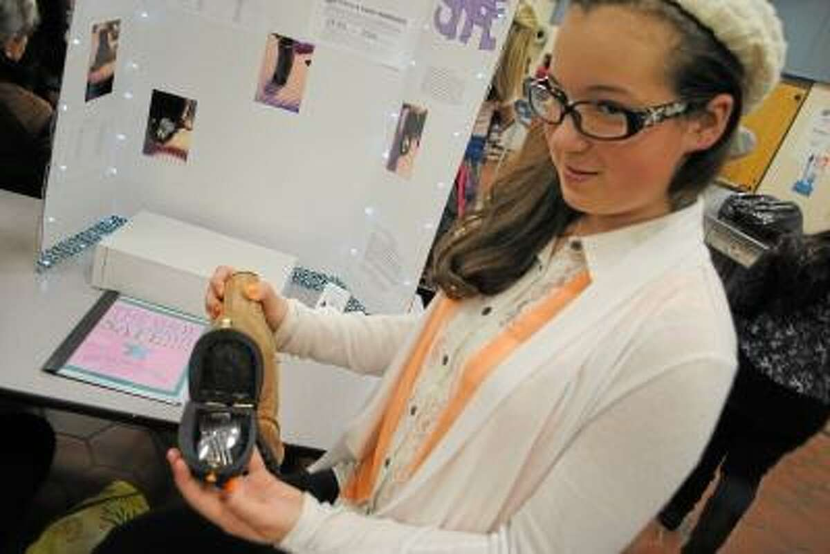"""Jessica Glenza/Register Citizen -- Torrington Middle School student Myla Carlson shows her invention, the """"Shoe Safe,"""" which keeps items safe in the sole of a boot."""