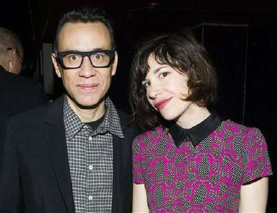 """FILE - This April 11, 2013 file photo originally released by IFC shows Fred Armisen, left, and Carrie Brownstein of the series """"Portlandia,"""" at IFC's 2013-14 Upfront Unexpectaganza in New York. The cable channel IFC said Wednesday it's picking up the show for two more seasons. They will premiere early next year and in 2015. Brownstein says the show will continue on the longer-narrative path, with more exploration of the dark side. (AP Photo/IFC, Charles Sykes, file) Photo: AP / IFC"""
