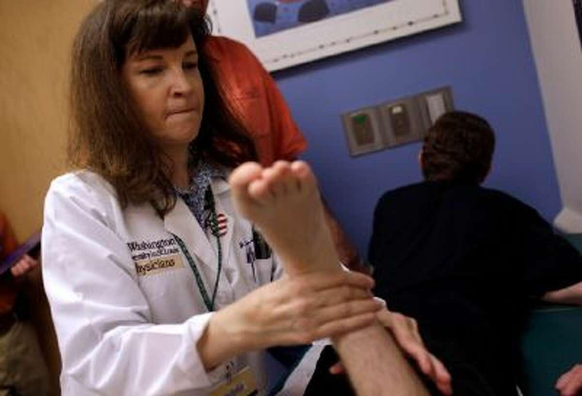 Dr. Jan Brunstrom-Hernandez, left, works with a cerebral palsy patient.