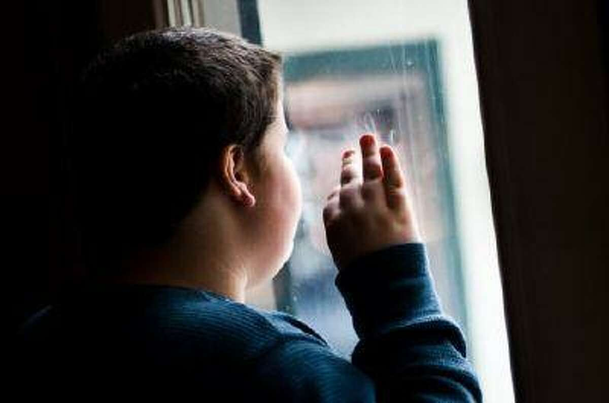 Twelve-year-old Christian Goff stops pacing for a moment to gaze out the window at his family s home near Spring Grove. Christian s mother, Kim Goff, says reetitive activites like pacing are typical of children, like her son, who have autism. (THE EVENING SUN/Clare Becker)