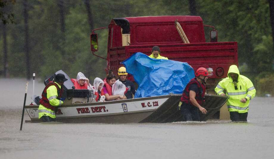 Porter fire fighters evacuate a family by boat from a neighborhood off East Knox Drive, Sunday, Aug. 27, 2017, in Porter. Photo: Jason Fochtman/Houston Chronicle