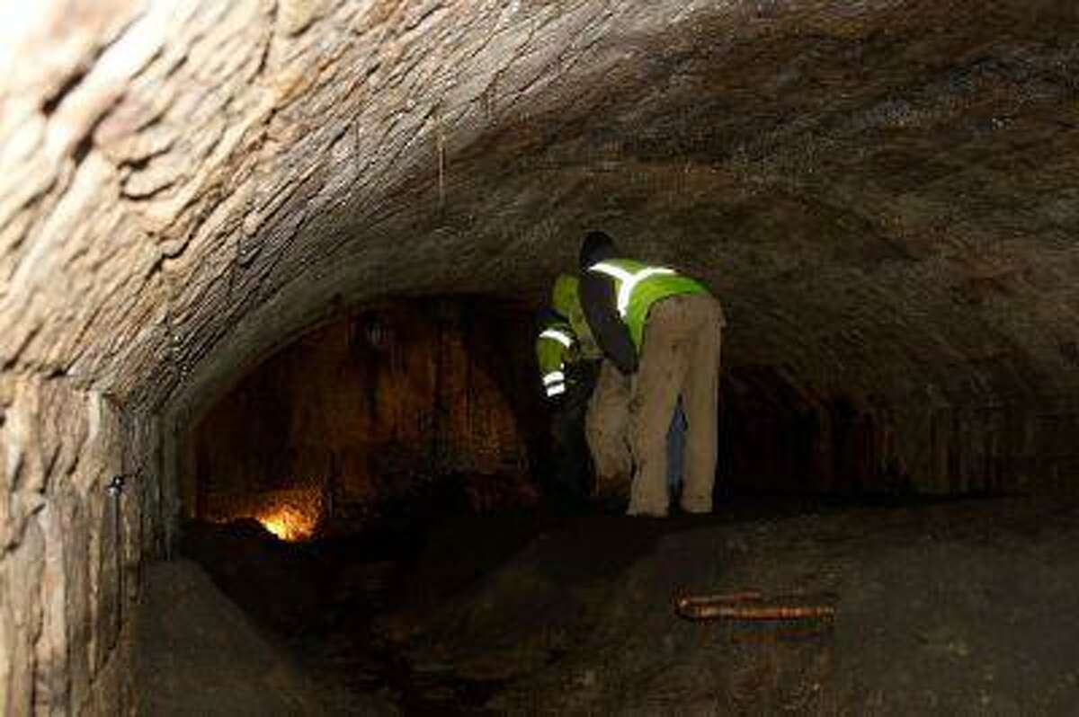 Amherst, Ohio, city workers inspect part of the long tunnel of the underground chamber found last week behind Amherst City Hall.