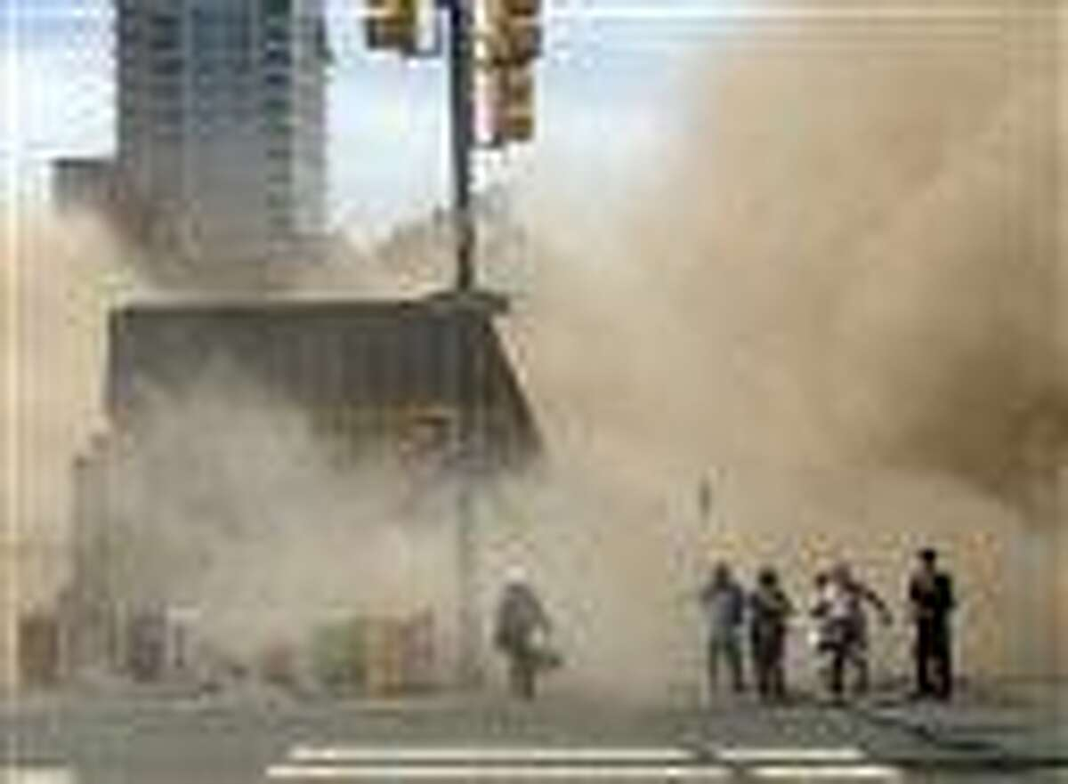 In this file photo provided by Jordan McLaughlin, a dust cloud rises as people run from the scene of a building collapse on the edge of downtown Philadelphia on Wednesday, June 5, 2013. An official says an inspector who surveyed a Philadelphia building before it collapsed last week, killing six people, has committed suicide. Deputy Mayor Everett Gillison says the inspector was found fatally shot in a pickup truck Wednesday night, June 12, 2013. The man was a Department of Licenses and Inspections employee who had inspected the building May 14. (AP Photo/Jordan McLaughlin, File)