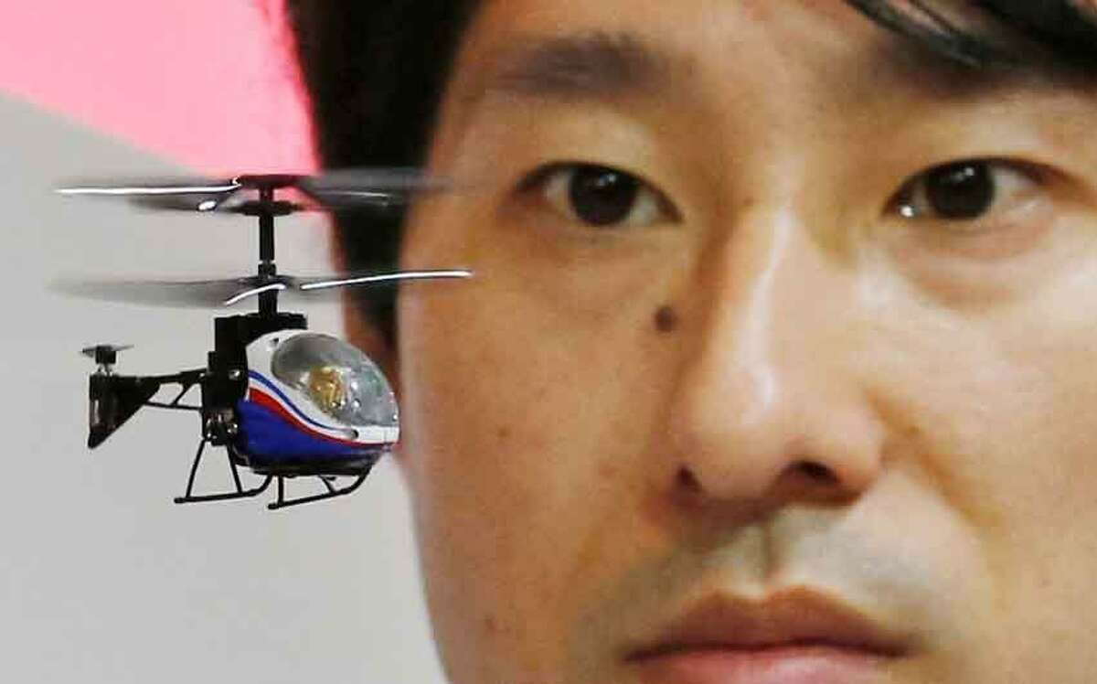 """A staff member of the Japanese toy and home appliances maker CCP Co. operates a """"Nano-Falcon,"""" the world's smallest infrared remote-controlled helicopter, at the Tokyo Toy Show in Tokyo Thursday, June 13, 2013. The toy helicopter measures 8 centimeter (3.1 inches) in length while weighing 11 grams (0.39 ounces). It's now on sale at 4,704 yen ($50) on the domestic market. (AP Photo/Koji Sasahara)"""