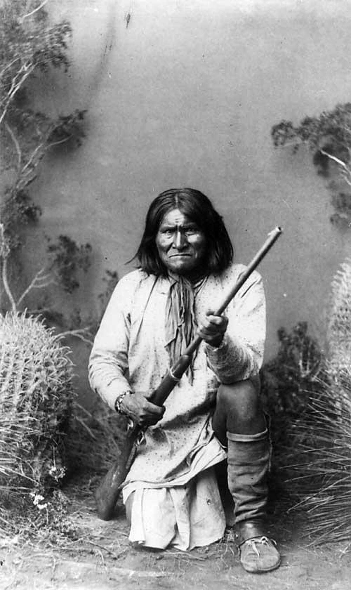 Geronimo, a Bedonkohe Apache, kneeling with rifle, 1887