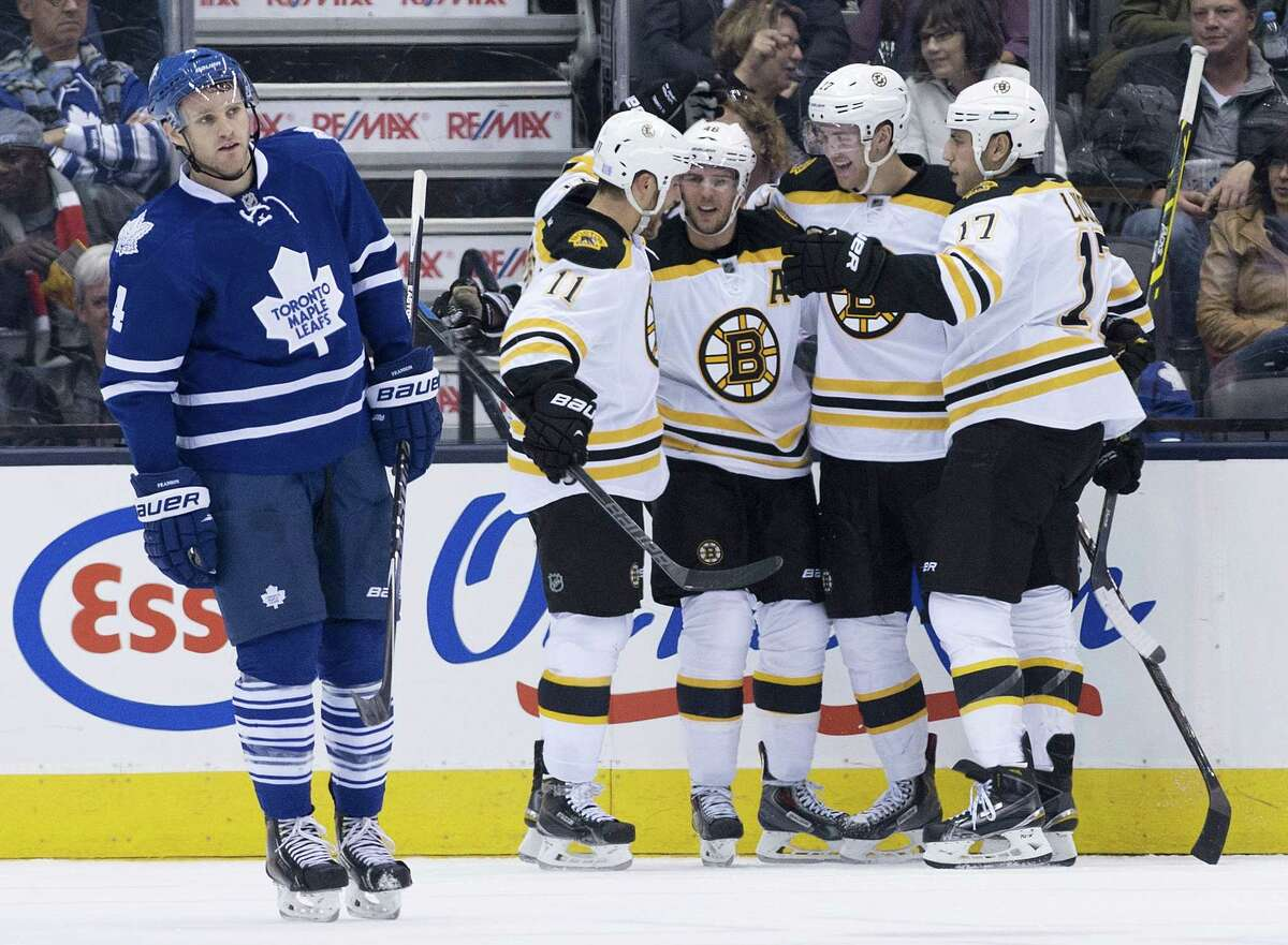 Maple Leafs defenseman Cody Franson, left, skates on as Boston Bruins forward David Krejci, center, celebrates his goal with teammates during the second period on Saturday in Toronto.