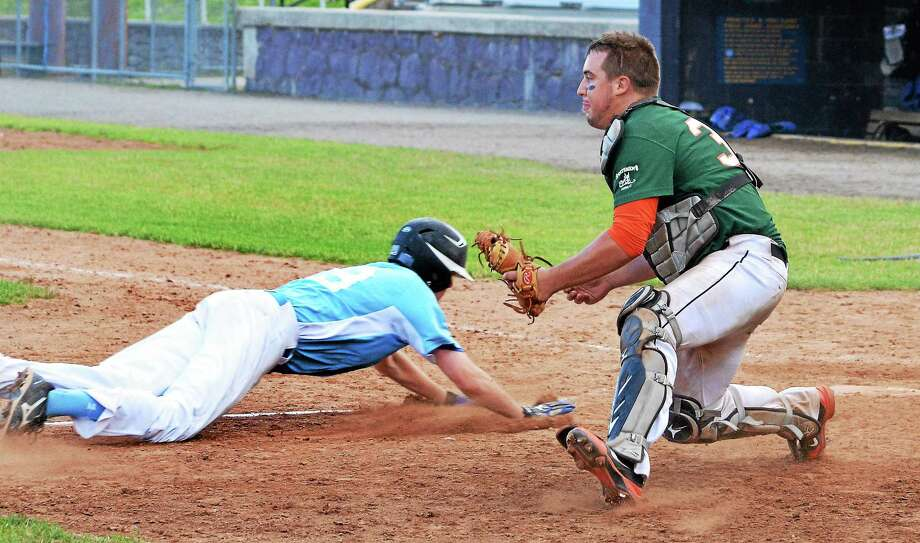 Burlington's Brady Hecht slides into home plate as Torrington's Greg Bodnar awaits the throw during a game at Fuessenich Park in Torrington. Photo: Register Citizen File Photo
