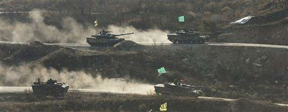 South Korean army K1 tanks move during an exercise at Seungjin Fire Training Field in mountainous Pocheon, South Korea, near the border with North Korea, Wednesday, March 27, 2013. North Korea said Wednesday that it had cut off a key military hotline with South Korea that allows cross border travel to a jointly run industrial complex in the North, a move that ratchets up already high tension and possibly jeopardizes the last major symbol of inter-Korean cooperation. (AP Photo/Yonhap, Lim Byung-shick) Photo: AP / Yonhap