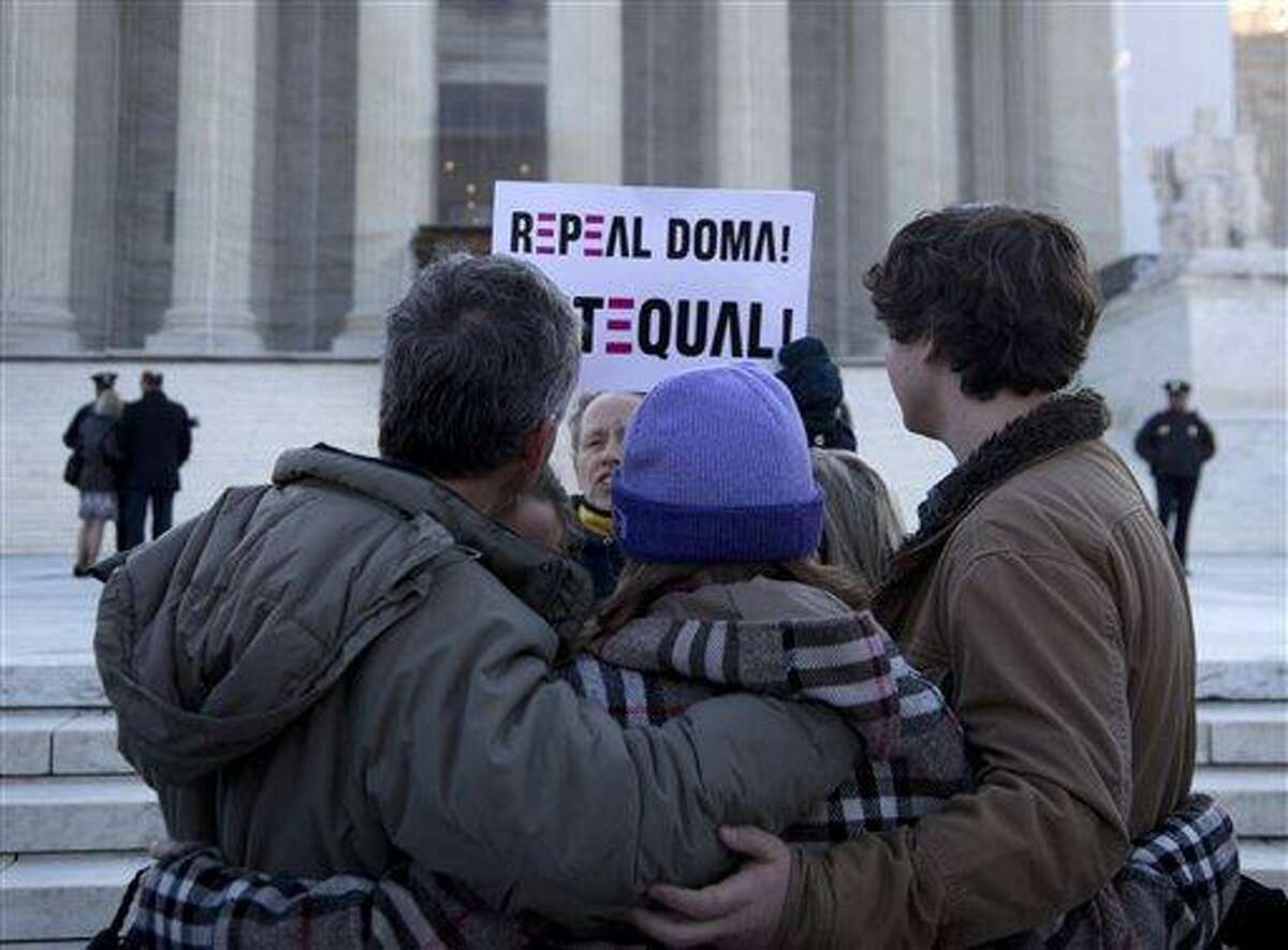 """A woman holds up a sign that reads """"REPEAL DOMA,"""" the Defense of Marriage Act, as a group from Alabama prays in front of the Supreme Court in Washington, Wednesday, March 27, 2013. In the second of back-to-back gay marriage case, the Supreme Court is turning to a constitutional challenge to the law that prevents legally married gay Americans from collecting federal benefits generally available to straight married couples. (AP Photo/Carolyn Kaster)"""