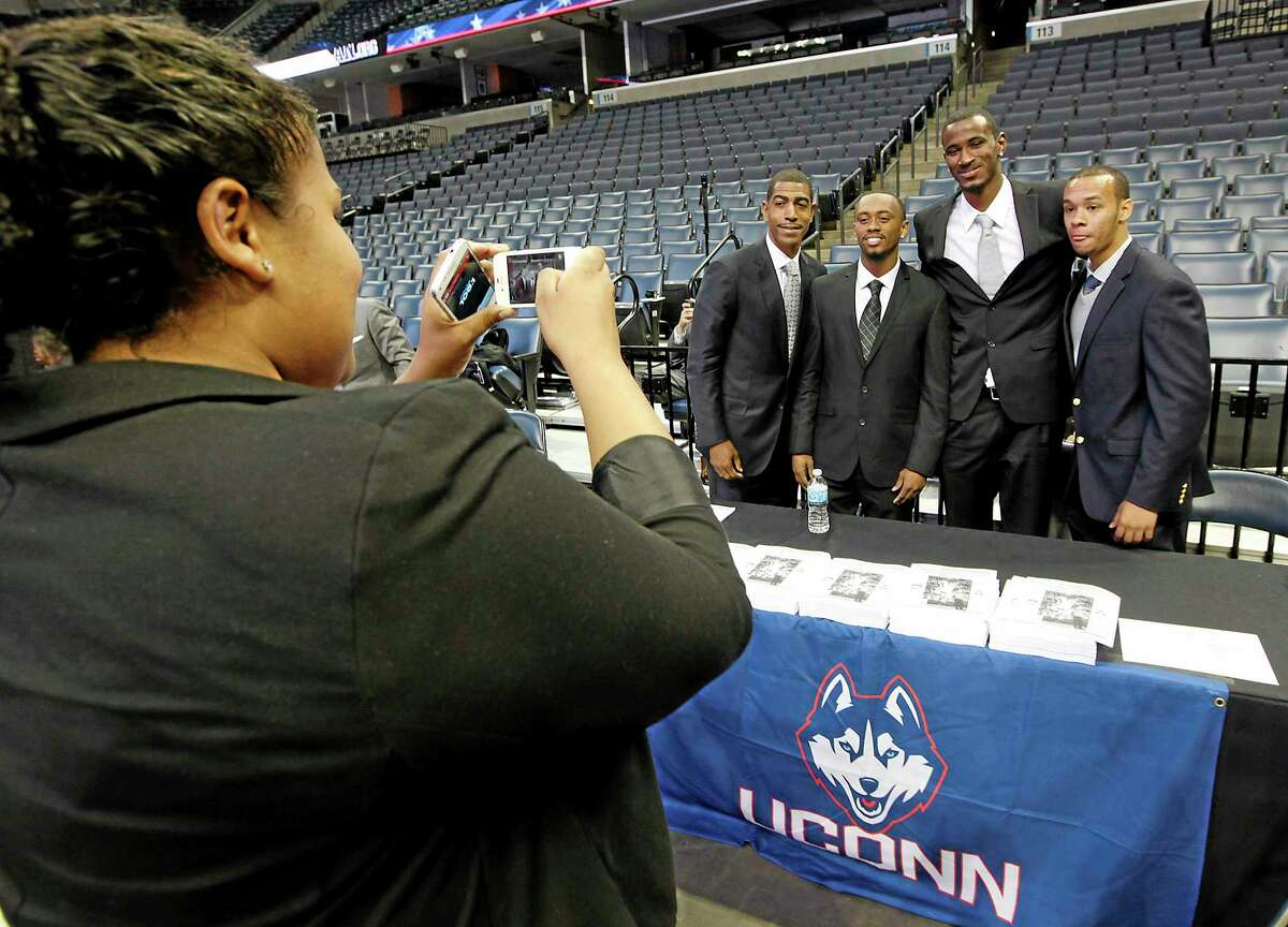 UConn coach Kevin Ollie, left, poses for a picture with Ryan Boatright, DeAndre Daniels and Shabazz Napier at the American Athletic Conference men's basketball media day on Wednesday in Memphis, Tenn.